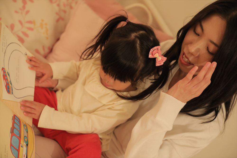 子供はお母さんのお膝で絵本を読んでおやすみ前の時間を過ごします。